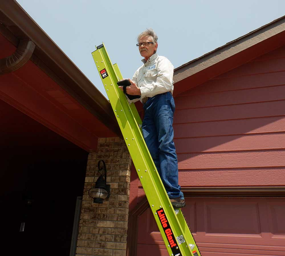 Craig Hall, one of our home inspectors, on a ladder inspecting the roof of a home